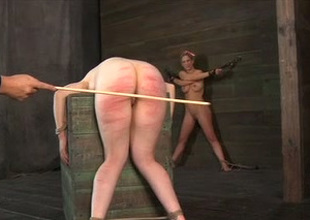 Depraved slavery master hits his slave's ass with a wooden try out
