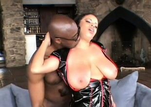 Busty as fuck tart in a vinyl corset gets filled with a dark dick