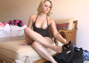 Blonde in pitch-black top removes her high heels and reaches out for vibrator