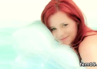 Redhead Ariel cooling her pussy in the pool