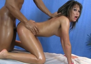 A brunette with a sexy face is getting massaged by her horny masseur