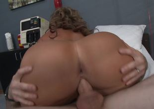 A curly blonde that loves to ride cock is fucked by the doctor