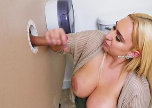 A blond is taking care of a cock through a glory hole