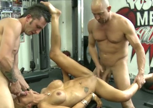 Blond haired bosomy MILF works on two strong dicks in the gym