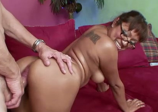 Mesmerizing milf in glasses rides a large white dick on the couch